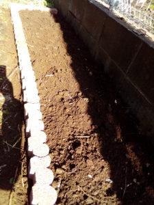 コンクリートブロックの周りの土を踏み固めて花壇が完成した写真